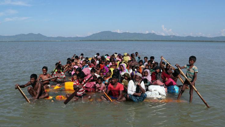 Rohingya refugees cross the Naf river with an improvised raft to reach Bangladesh at Sabrang near Teknaf