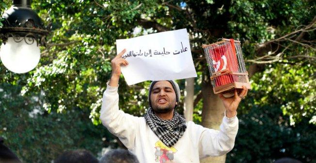 Sarah Leduc _Sulla viale Bourguiba di Tunisi, un uomo ha messo una bandiera in gabbia domenica_14 gennaio_come simbolo della Tunisia ai tempi di Ben Ali