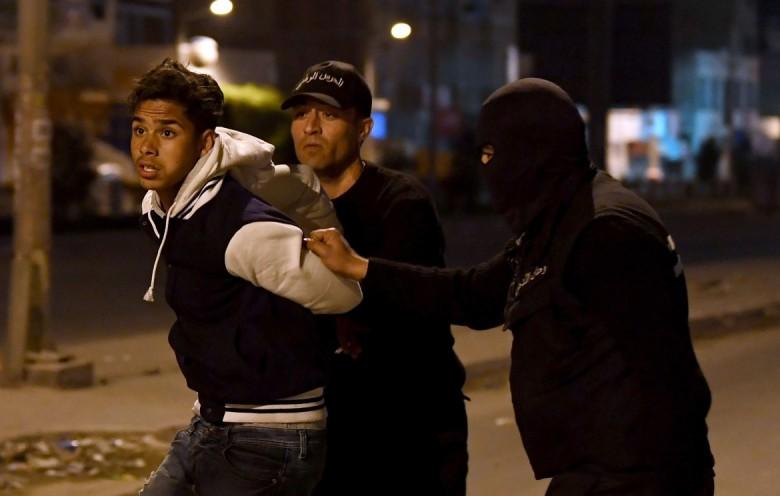 Un giovane tratto in arresto a Ettadhamen, sobborgo di Tunisi © LaPresse