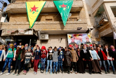 Kurdish civilians perform traditional dance as they celebrate, reports of Kurdish forces taking control of Syrian town of Kobani, in Sheikh Maksoud neighborhood of Aleppo