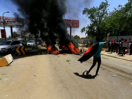 A Sudanese protesters gestures as they burn tyres and barricade the road leading to al-Mek Nimir Bridge crossing over Blue Nile; that links Khartoum North and Khartoum
