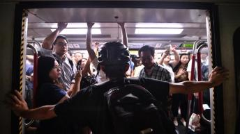 A protester blocks an underground commuter train from closing in Hong Kong on Monday _Anthony Wallace_AFP