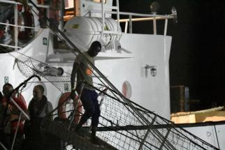 A man disembarks from the Open Arms rescue ship on the Sicilian island of Lampedusa, southern Italy, Tuesday, Aug. 20, 2019. An Italian prosecutor ordered the seizure of a rescue ship and the immediate evacuation of more than 80 migrants still aboard, capping a drama Tuesday that saw 15 people jump overboard in a desperate bid to escape deteriorating conditions on the vessel and Spain dispatch a naval ship to try to resolve the crisis. (AP Photo/Salvatore Cavalli)
