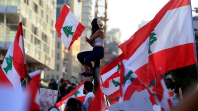 A demonstrator sits on a pole while carrying a national flag during an anti-government protest in downtown Beirut_ Lebanon October 20_ 2019_Ali Hashisho_Reuters