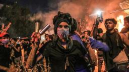 Un manifestante indossa bombole di gas lacrimogeni sulle dita e indica il segno della vittoria durante le proteste antigovernative nella città di Karbala _AFP