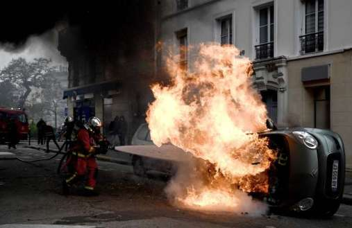 "A firefighter tries to extinguish a burning car on place d'Italie in Paris on November 16, 2019, on the sidelines of a demonstration of the ""yellow vest"" (gilets jaunes) marking the first anniversary of the movement. French ""yellow vest"" protesters are planning a series of nationwide demonstrations this weekend in a bid to show the government they can still muster support on the first anniversary of their movement. Numbers attending the protests and levels of violence have sharply diminished in recent months from the height of the movement, which began on November 17 last year with a giant Paris protest that drew almost 300,000 people. / AFP / Philippe LOPEZ"