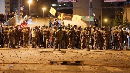 I sostenitori dei gruppi sciiti Hezbollah e Amal portano bandiere mentre i soldati dell'esercito libanese li separano dai manifestanti antigovernativi a Beirut _Mohamed Azakir _ Reuters
