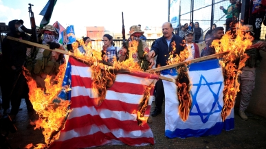 Demonstrators set fire to makeshift Israeli and US flags during a protest against Trump's Middle East plan in Ain al-Hilweh Palestinian refugee camp _Ali Hashisho_Reuters