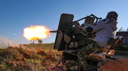 Mercoledì scorso un combattente siriano appoggiato dalla Turchia spara un fucile montato su camion verso la città di Saraqeb_Omar Haj Kadour_ AFP