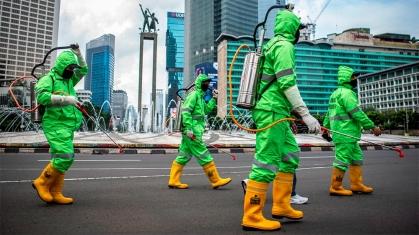 lavoratori camminano in tute protettive durante un'operazione di spruzzatura di disinfettante a Jakarta_ Indonesia _Reuters