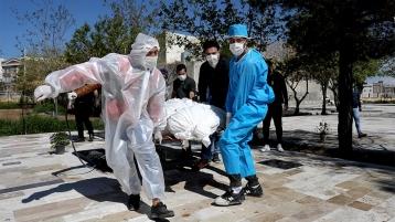 Le persone che indossano indumenti protettivi portano il corpo di una vittima di coronavirus _Ebrahim Noroozi _ AP