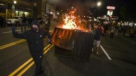 La gente sposta un cassonetto in fiamme verso una fila di poliziotti durante il quarto giorno consecutivo di proteste a Denver_in Colorado_Michael Ciaglo_Getty Images_AFP