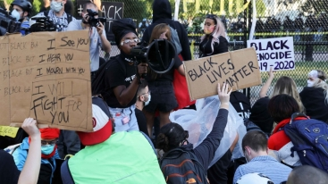 Un manifestante si rivolge alla folla riunita davanti a una recinzione che circonda il Parco Lafayette fuori dalla Casa Bianca, a Washington, DC, Stati Uniti_Jonathan Ernst _ Reuters